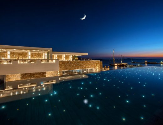 Spotlights in the pool of Mykonos Riviera hotel overlooking the sea at dusk.
