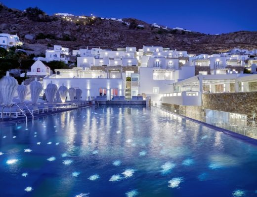 The facade of Mykonos Riviera overlooking the pool with spotlights at night.