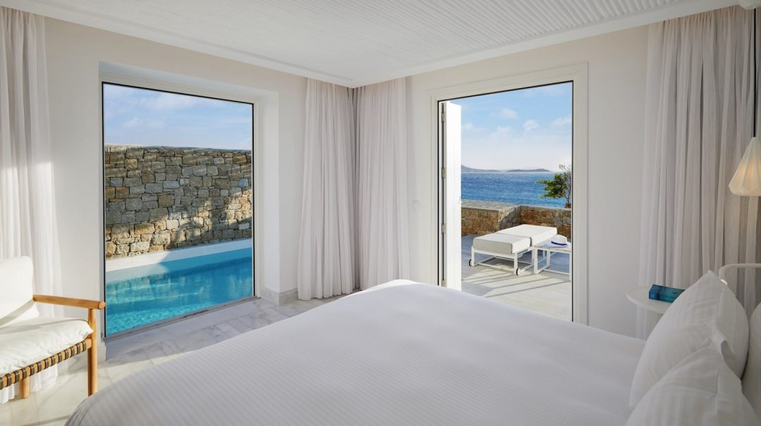 Double bed in a bedroom with two open windows leading to a private pool area in Mykonos Riviera.